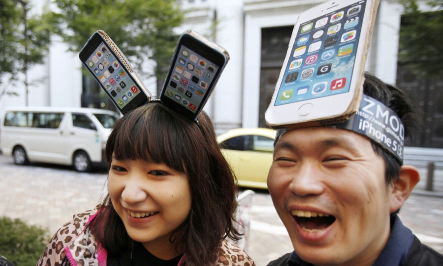 Yui Kashima, left, and Nobuhiko Matsuda wait to purchase an Apple's new iPhone outside a store in Tokyo on Friday morning, Sept. 20, 2013. Apple released the latest iPhones 5C and 5S on Friday. (AP Photo/Koji Sasahara)
