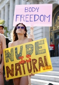 "A woman, who would not give her name, holds a sign saying ""Nude is Natural,"" during a rally against banning nudity in parts of the city in San Francisco, California, November 14, 2012. REUTERS/Beck Diefenbach (UNITED STATES - Tags: CIVIL UNREST POLITICS SOCIETY)"