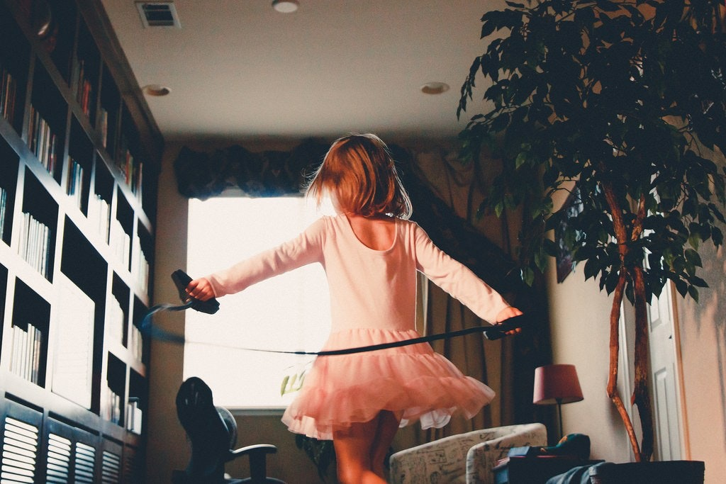 A girl in a tutu dancing in a living room