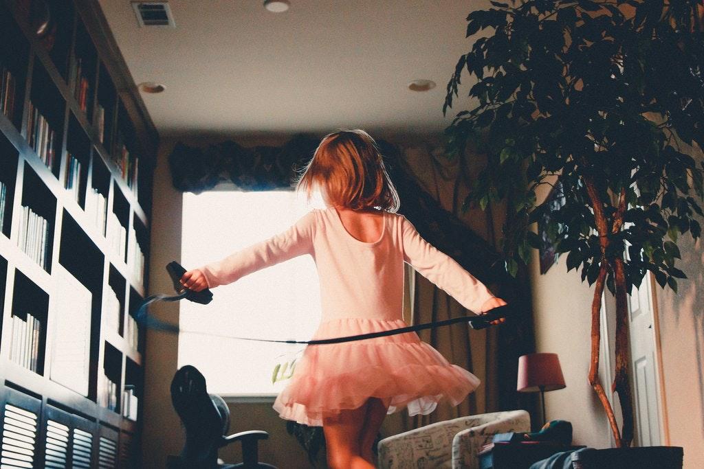 A girl in a tutu dancing in a living room