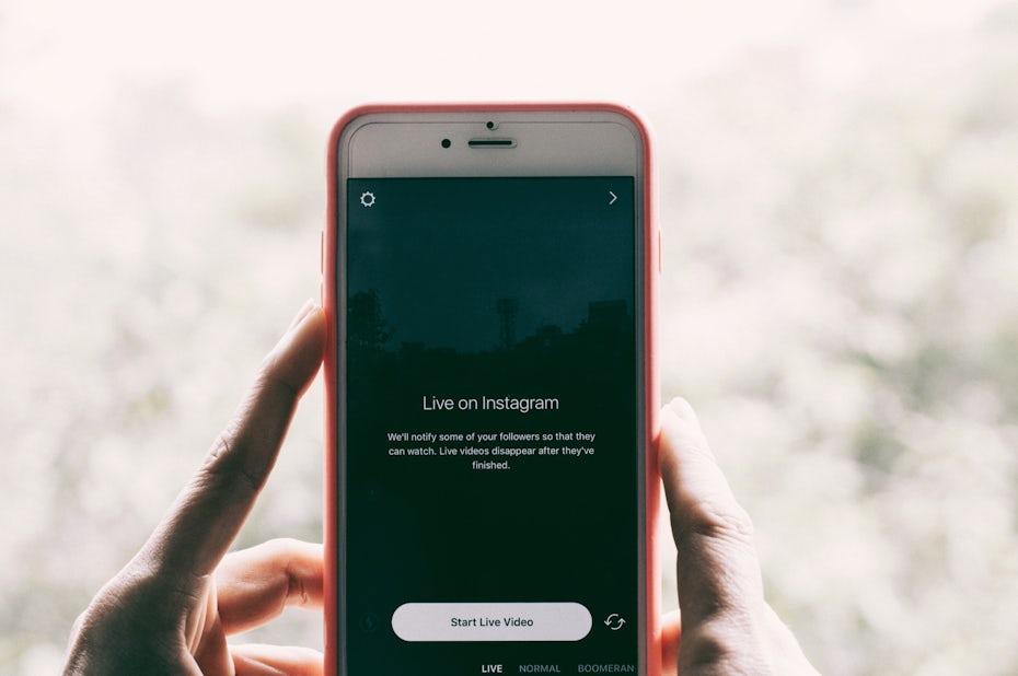 Sosteniendo un teléfono a punto de hacer un video en vivo en Instagram