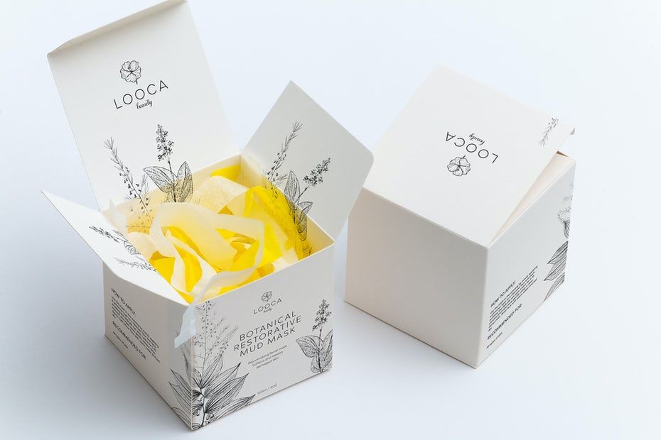 white packaging with intricate floral drawings