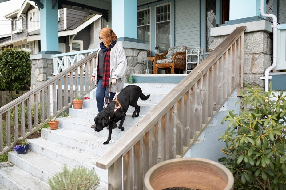 girl with dog walking down stairs