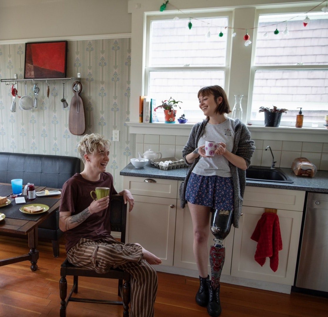 A woman with a prosthetic leg drinking coffee, talking with boyfriend in kitchen