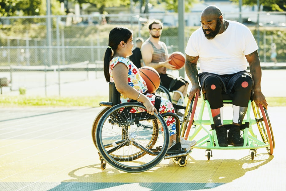 Smiling young female adaptive athlete getting advice from adaptive basketball coach during practice on summer evening