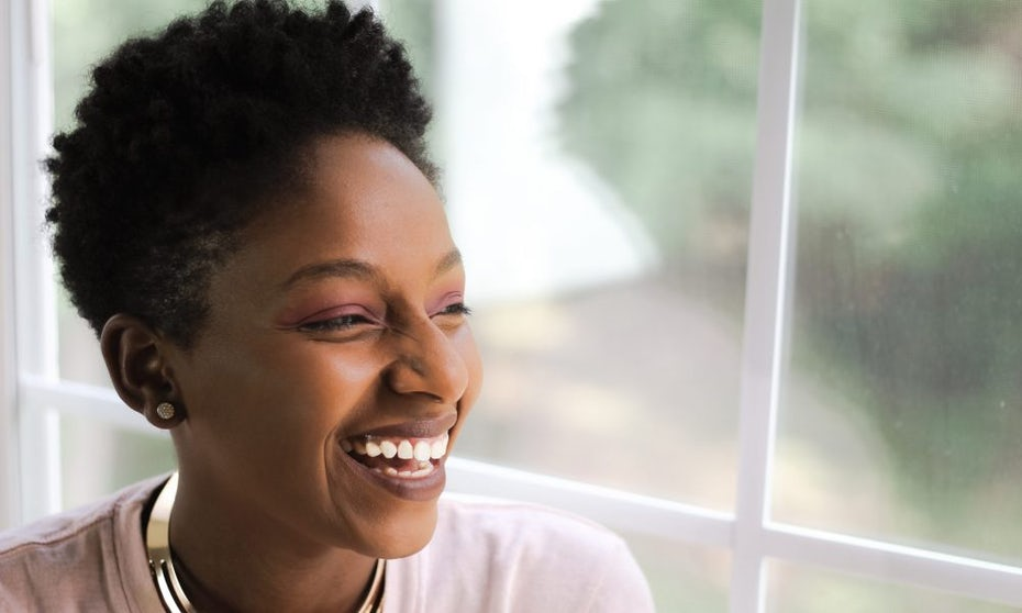 A photo of CreateHERStock founder Neosha Gardner, smiling and looking out the window