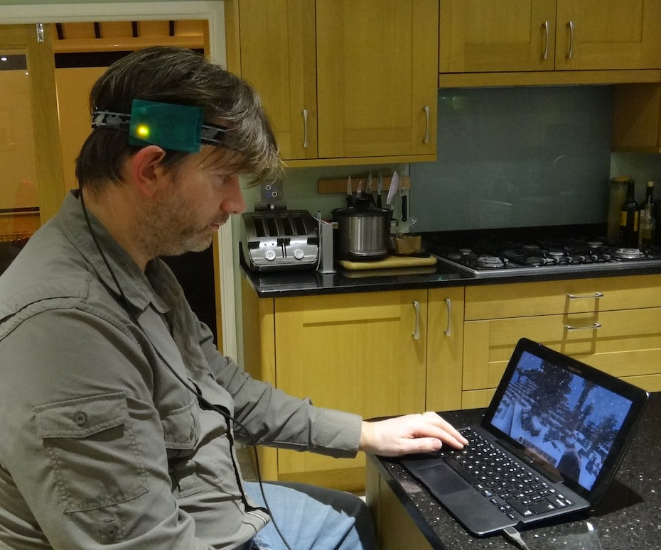man using a head-movement direct access system to play a game on a laptop