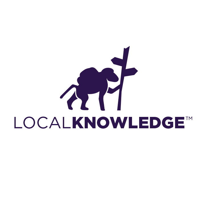 silhouette of a baboon with a backpack standing by a signpole