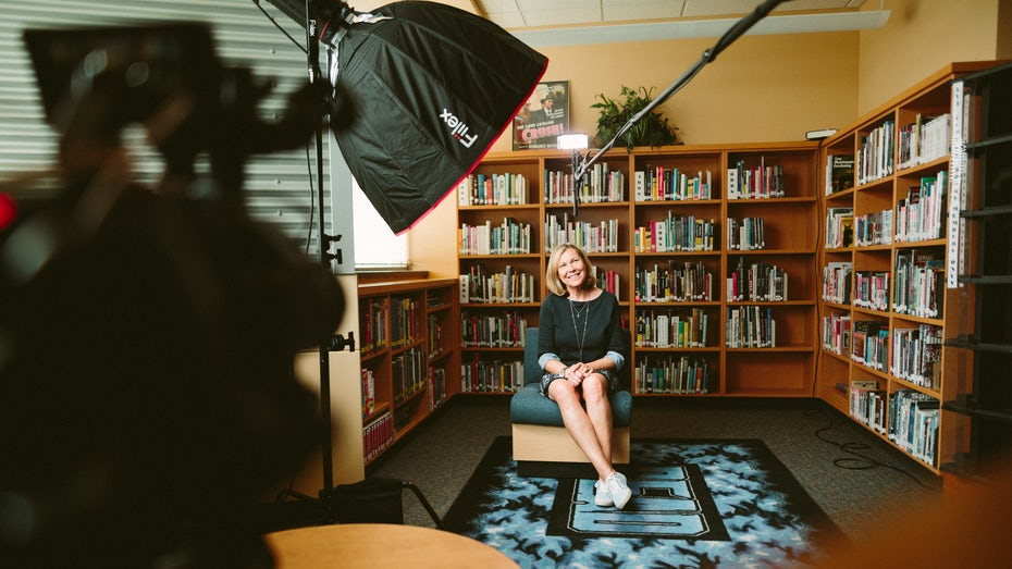 A video production of a person being interviewed in a library