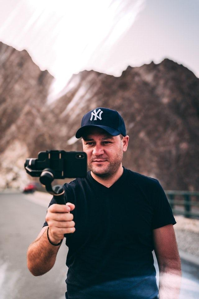 Ejemplo de tendencia de marketing digital 2020: hombre tomando selfie con selfie-stick