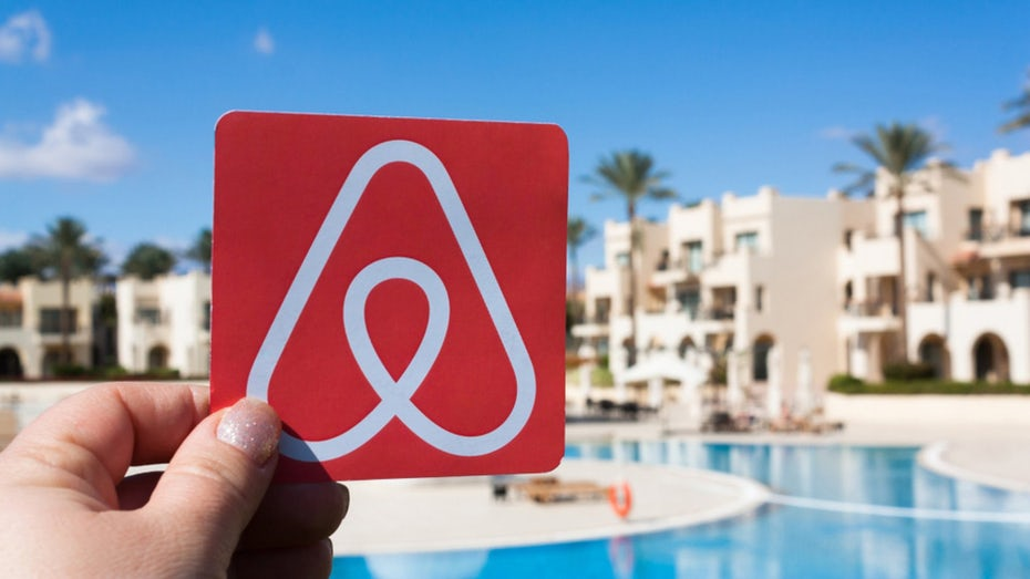 Hand holding an image of the AirBnB logo in front of a swimming pool