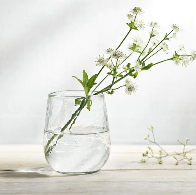 Small while flowers in a wine glass with white background