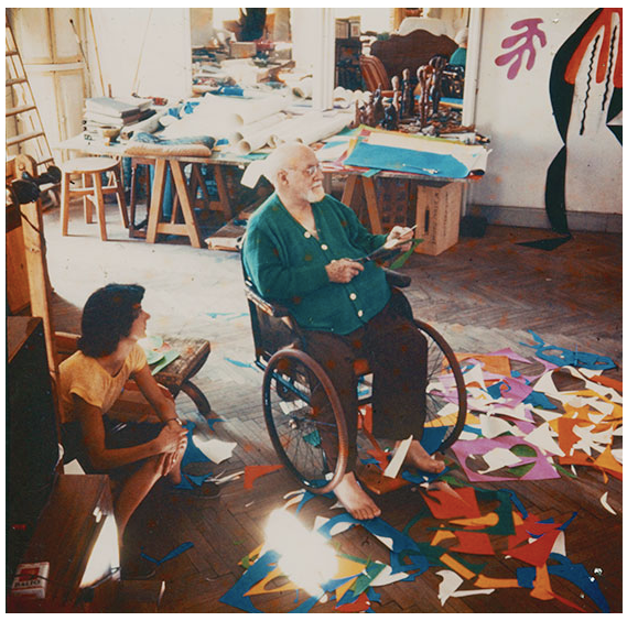 photograph of Henri Matisse creating The Cutouts as another person looks on
