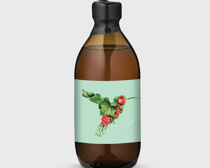 bottle label showing a hummingbird created with smaller images of leaves and berries