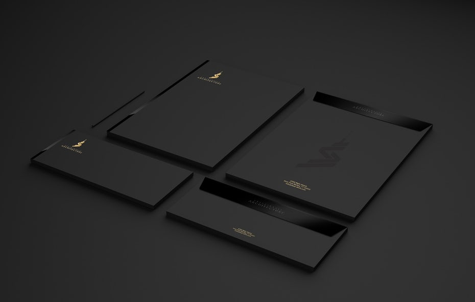 black and white stationary with an embossed logo and a gold corner logo