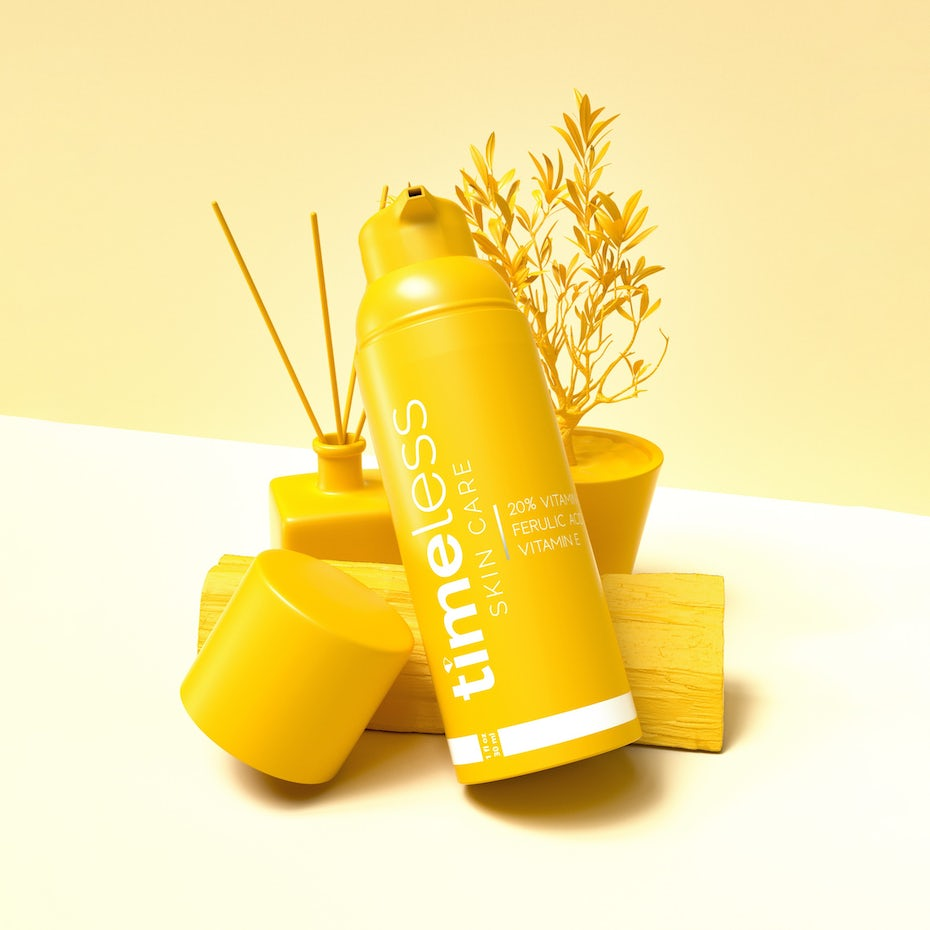 mockup of a yellow cosmetics bottle laid against a plant, a diffuser and a block of wood
