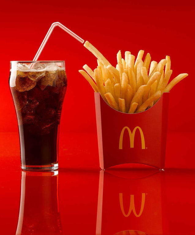 glass of coke next to a McDonald's french fries against a red background