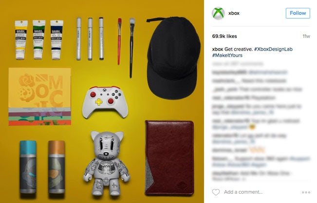knolling image of an xbox controller alongside art supplies and a hat