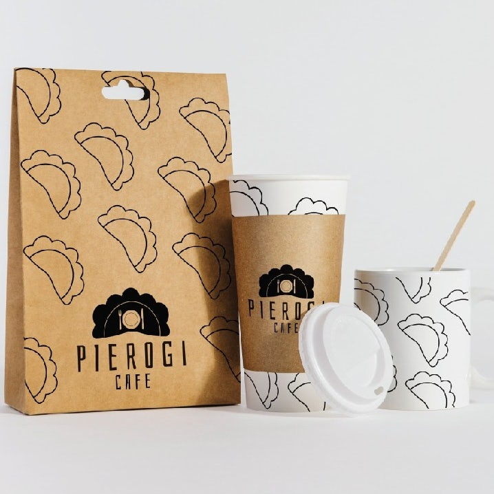 brown paper bag with line illustrations of pierogies alongside a paper coffee cup and a mug