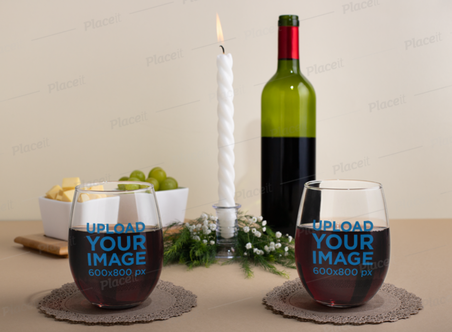 two stemless wine glasses on a table with a wine glass and a candle