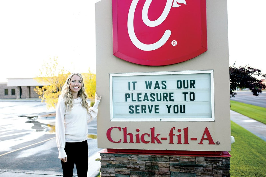 photo of a woman standing beside a Chick Fil A sign