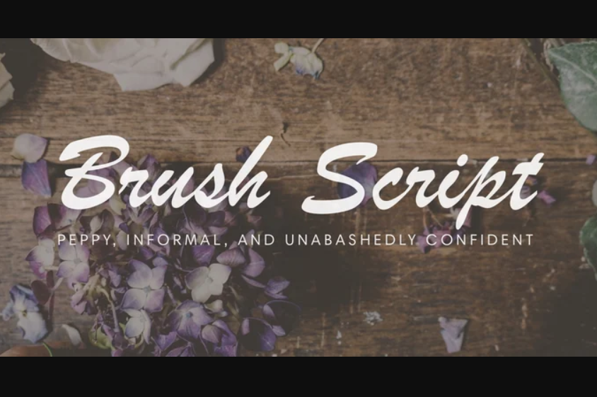 Brush Script font against wooden table background with purple flowers