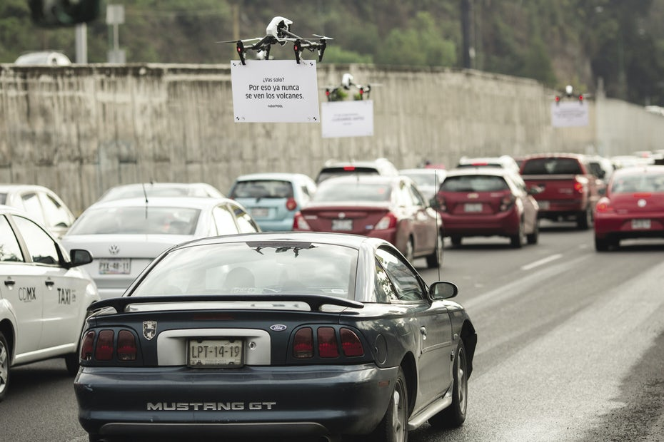 car stopped in traffic, a drone holding a sign in front of the windshield