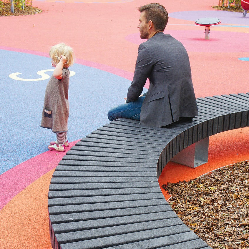 father sitting on a plastic playground bench while watching his child