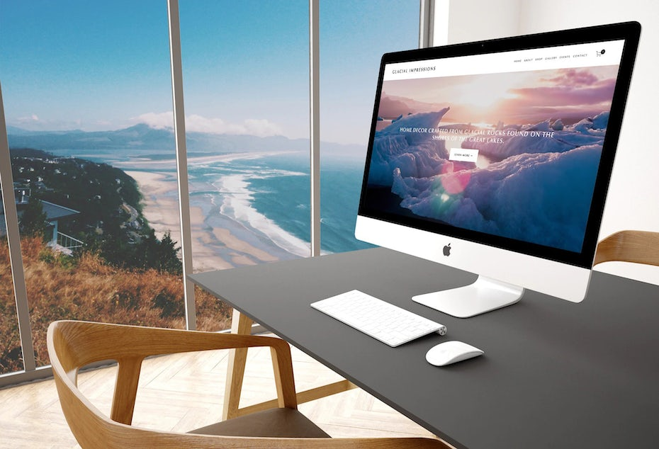 a computer with ecommerce website on the screen at a desk with a sea view