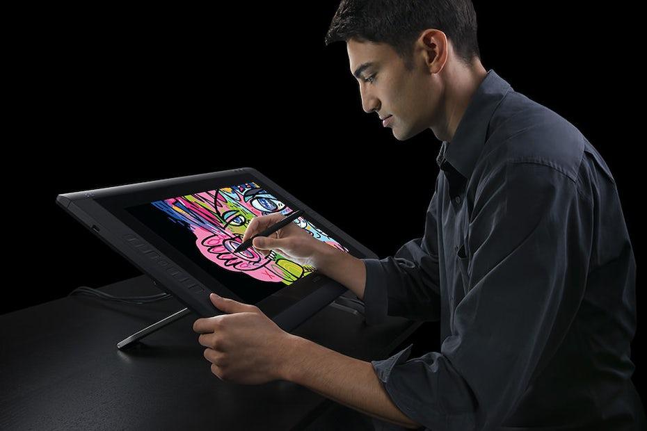 man sitting at a Wacom Cintiq 22, drawing