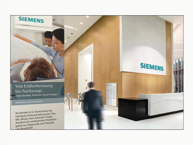 a building lobby showing a reception area with the Siemens old logo on a large white panel