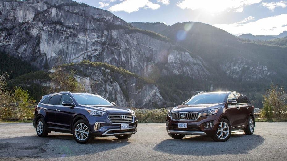 a side-by-side comparison of Hyundai Santa Fe in black and Kia Sorento in maroon