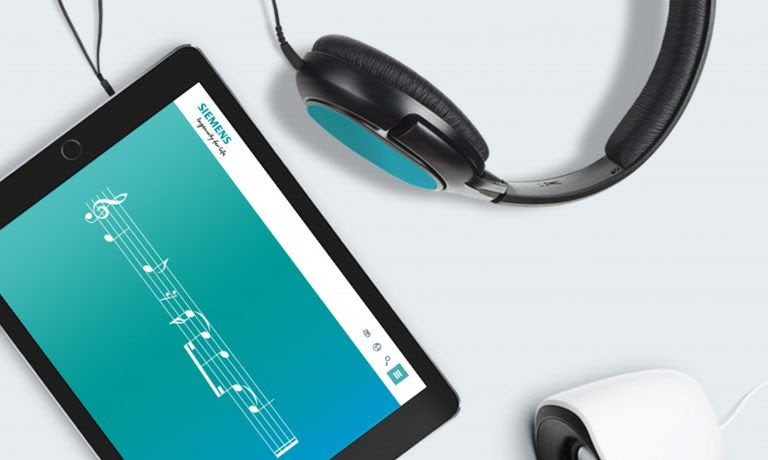 a tablet is open with the musical notes to Siemens' audio branding on display, and a black and blue headphones on the side