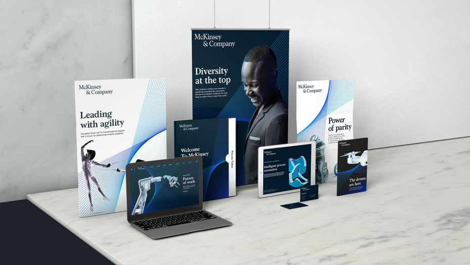 a laptop, tablet, folders, brochures, and banners are displayed with the new brand design