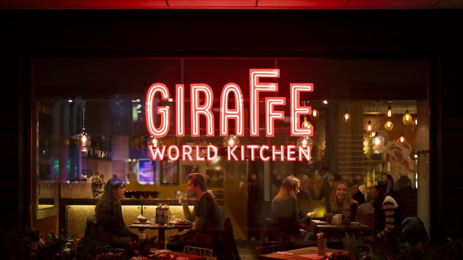 a glass window from the outside looking into a restaurant with a large Giraffe World Kitchen sign in red neon lights