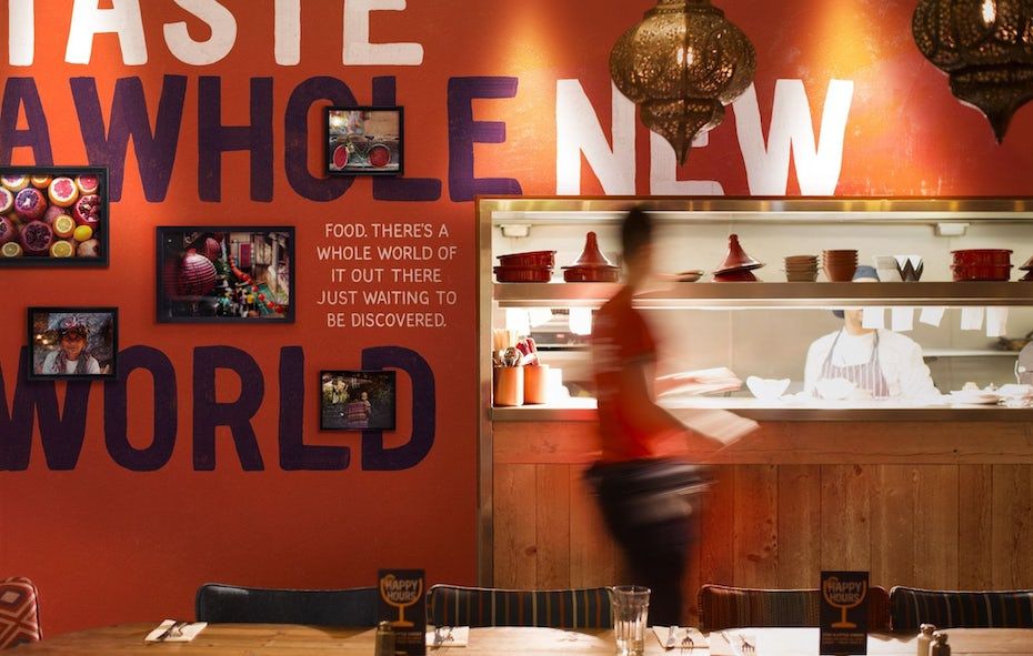 an interior view of a kitchen counter backdropped against an orange wall filled with photographs