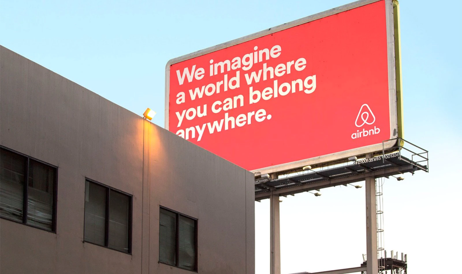 an airbnb billboard in coral pink and a text that says: we imagine a world where you can belong anywhere.