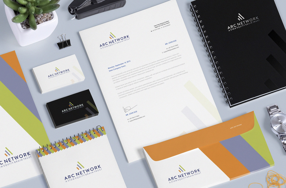 a table full of business cards and office stationeries, like a black notebook, an envelope with orange, blue, and green stripes, and a company letterhead